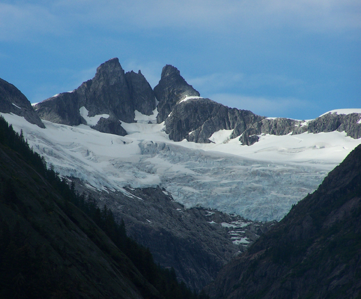 A light blue glacier covered with snow sits suspended on a steep mountain slope as pointed peaks extrude out the top.